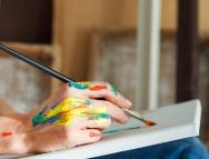 Close up of female artist hand holding paintbrush